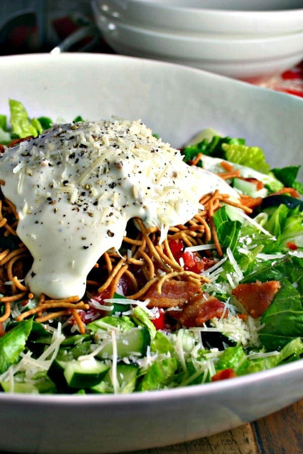 Insalata Della Casa in a bowl with creamy dressing and parmesan cheese