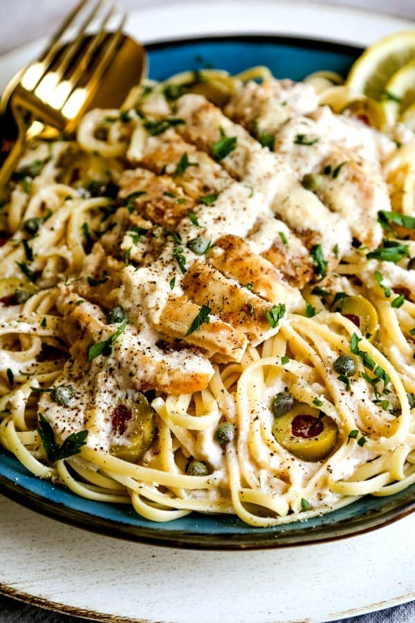 lemon chicken on top of a plate of pasta