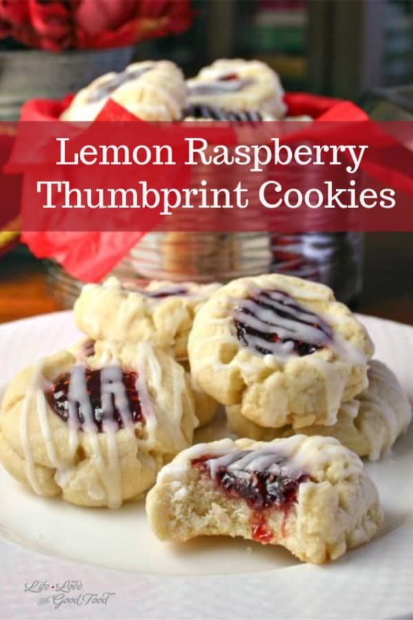 lemon raspberry thumbprint cookies on a white plate with a tin of cookies in the background