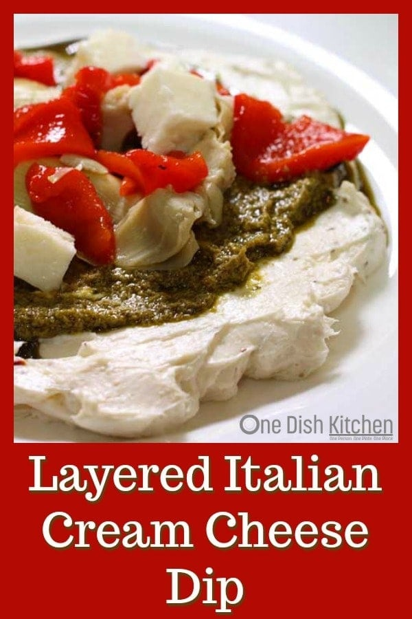 Layered Italian Cream Cheese dip, an easy to make spread topped with pesto, artichoke hearts, roasted red peppers and mozzarella cheese. | One Dish Kitchen | #holiday #holidayrecipes #Christmas #dips #party #appetizer #pesto
