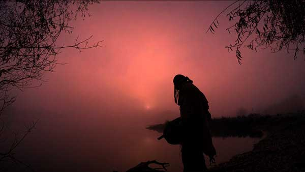 Schamane im Morgenrot am Wasser