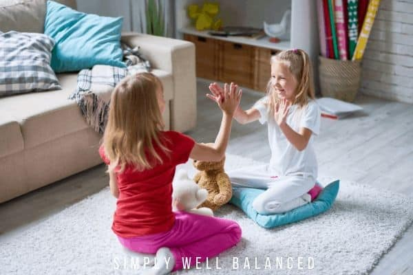 Two girls playing hand clapping games on the living room floor