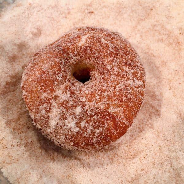 Apple Cider Donuts being rolled in cinnamon sugar