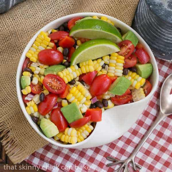 Overhead view of Fresh Corn and Black Bean Salad in a white bowl on a red and white checked napkin