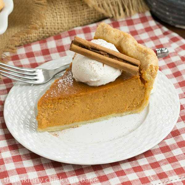 Classic Pumpkin Pie slice topped with whipped cream and garnished with a cinnamon stick