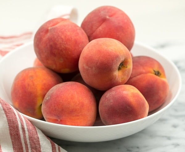 A white bowl full of red haven peaches