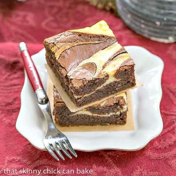 Ricotta Cheesecake Brownies stacked on a square white plate