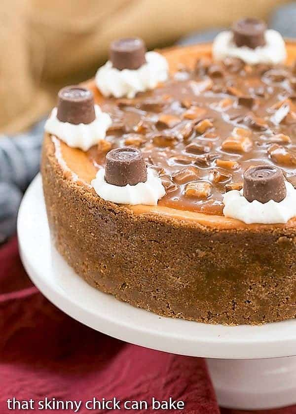 Caramel Cheesecake on a white cake plate topped with caramel sauce, toffee, whipped cream roses and Rolo candies