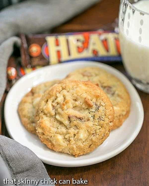 White Chocolate Toffee Chunk Cookies on a white ceramic plate with a glass of milk