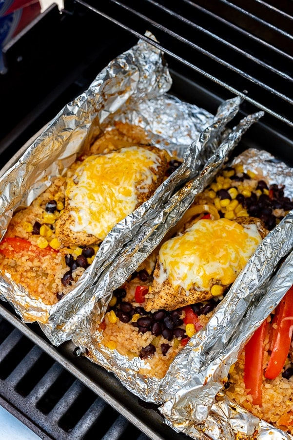 Foil packets filled with chicken and vegetables on the grill.