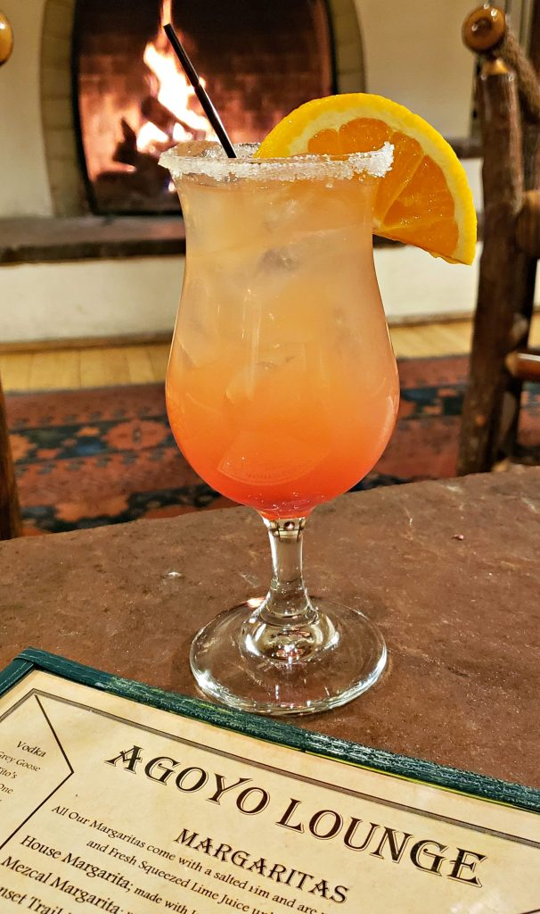 Margarita in hurricane glass sits on table in front of fireplace - colors are like the sunset