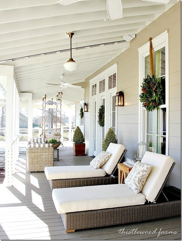 Topiaries, lounge chairs and magnolia wreaths give this gorgeous back porch a comforting style