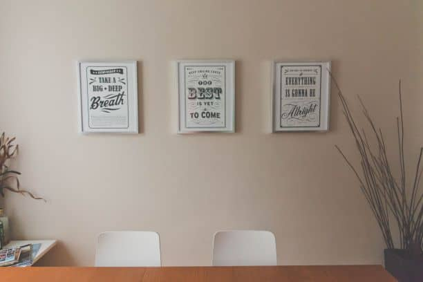 3 same-size frames on wall over two chairs at table
