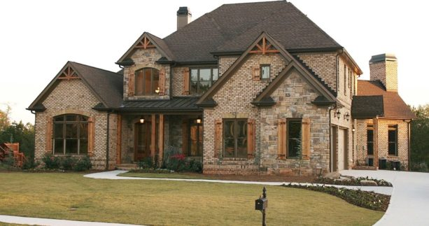 brown brick home exterior with wood-color shutters