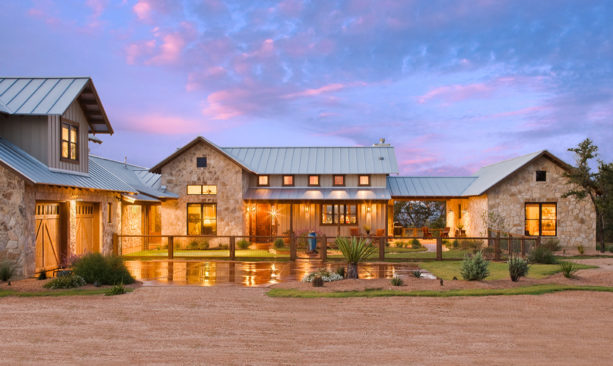 example of ranch style stone exterior home design with vinyl siding and metal roof
