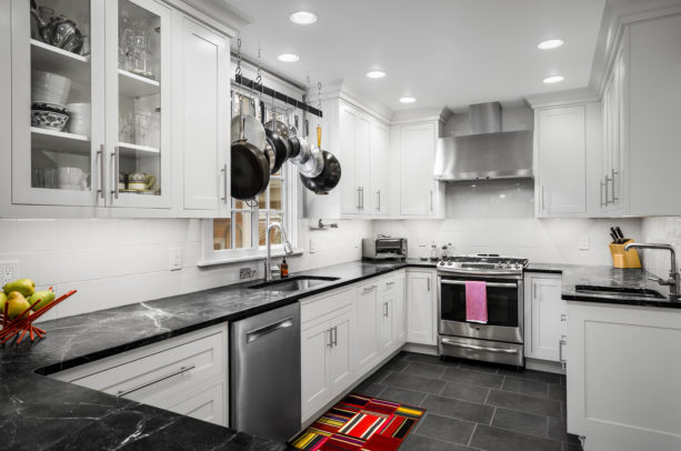 small yet classy kitchen with white cabinets and backsplash combined with ebony black countertops