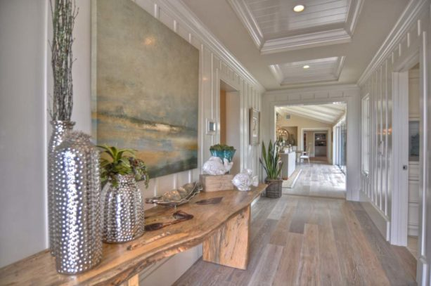 a beach-style hall with shiny white trim and greyish wood floor