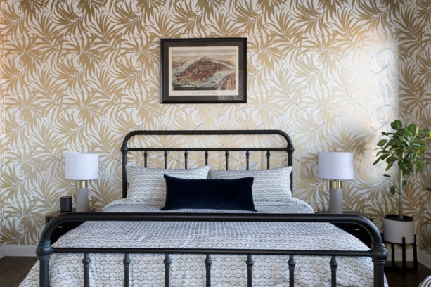 a black contemporary metal bed placed in front of a gold leaves accent wall