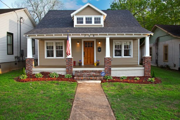 a craftsman-style house with tan siding and red brick columns