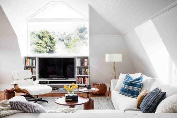 a TV placed inside a custom white entertainment center with bookshelf feature