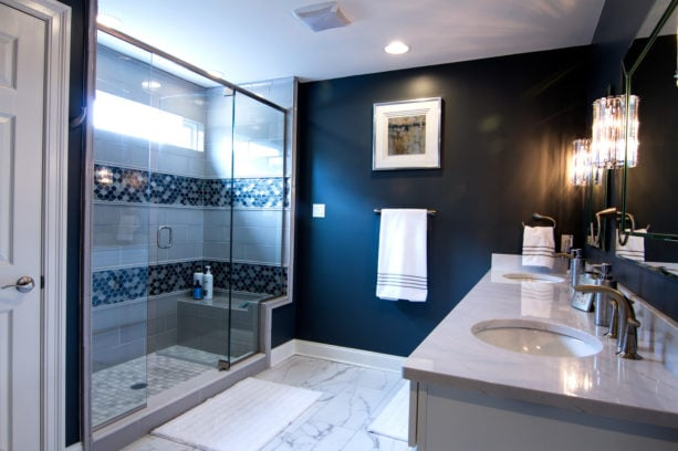 a luxurious bathroom with navy blue focal point wall combined with white countertop