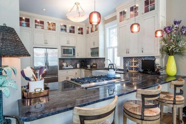 elegant u-shaped kitchen with a peninsula and three bar stools