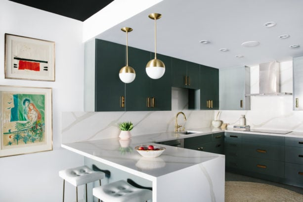 green kitchen cabinets and a peninsula with calacatta gold countertop in a u-shaped layout