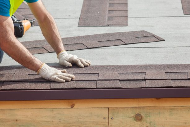 covering the sheathed roof with shingles