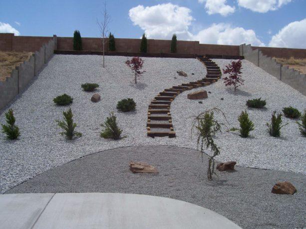 desert white gravel backyard landscape idea in a steep slope