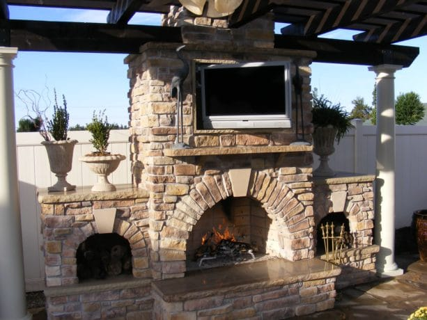 custom designed wood burning fireplace to accommodate an outdoor rated tv