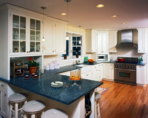 blue black soapstone countertops in spotless white cabinets for a farmhouse kitchen