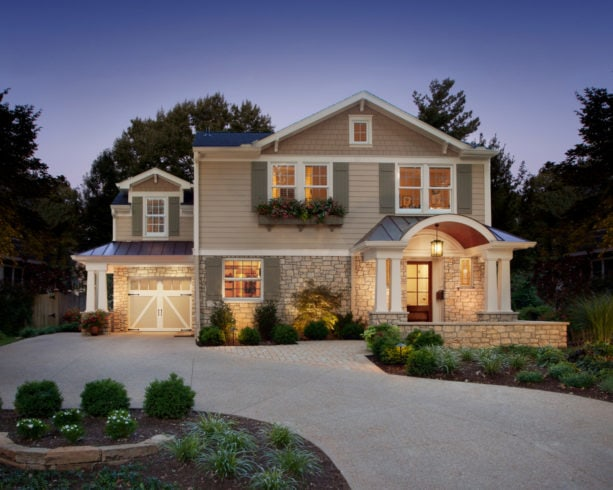 transitional garage with double side-hinged door and stone paved carport at the front