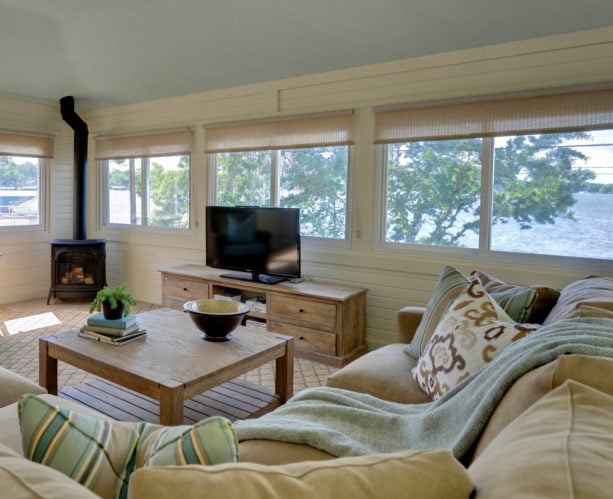 a transitional sunroom with roll-up woven blinds to reduce glare and heat for better TV-viewing