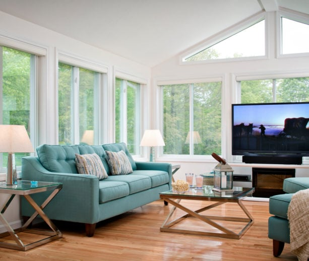 a large traditional sunroom with a large TV in front of the window
