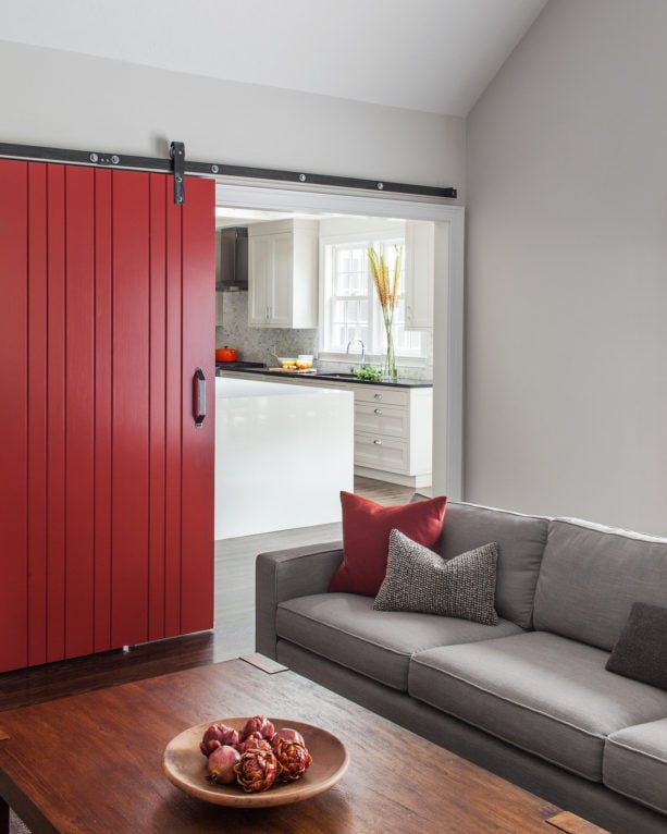 catchy red sliding door that separated a grey living room with the kitchen next to it