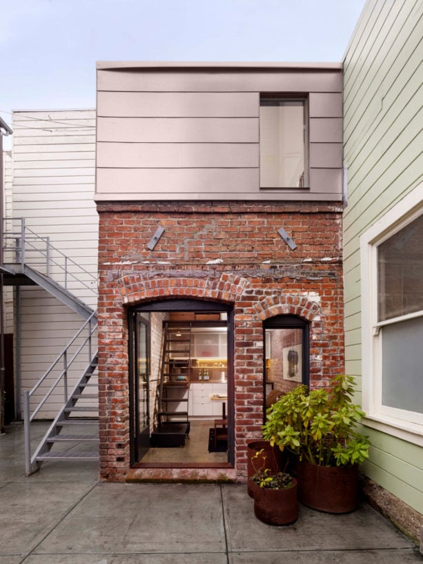 a charming contemporary facade with tan siding and red brick combination