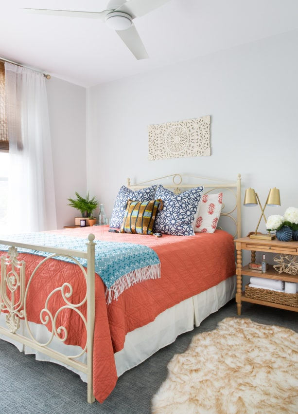 a coral bedding and blue blanket to update a bedroom look