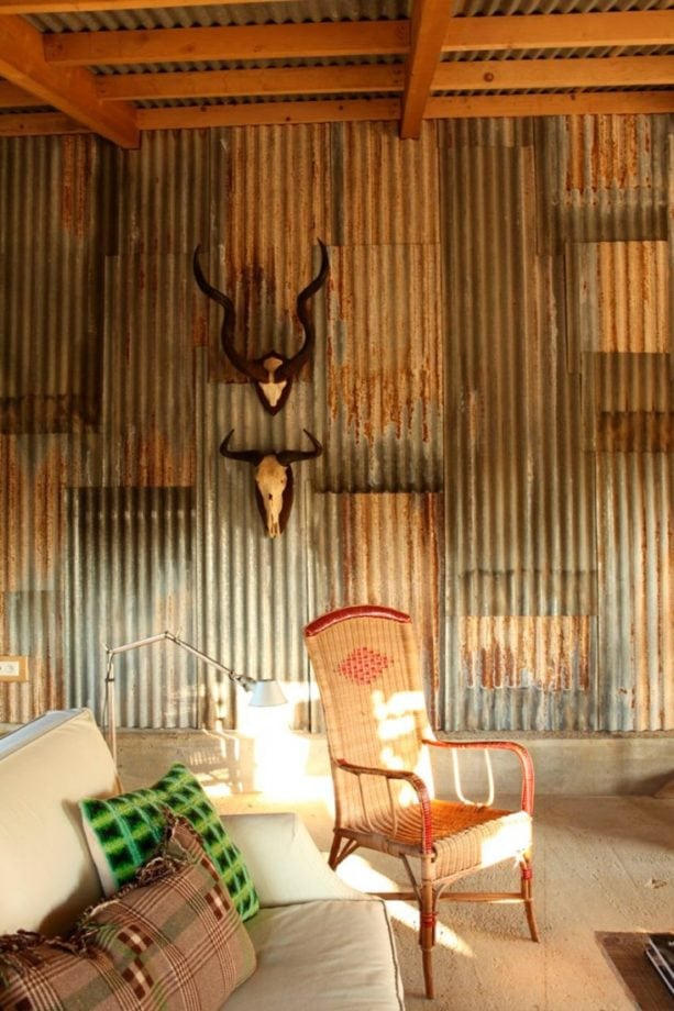 a rustic living room wall covered by reclaimed corrugated metal panels