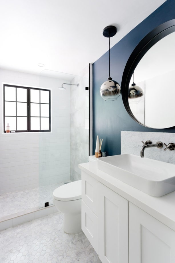 a small transitional clean bathroom with dark blue and white combination to look fierce