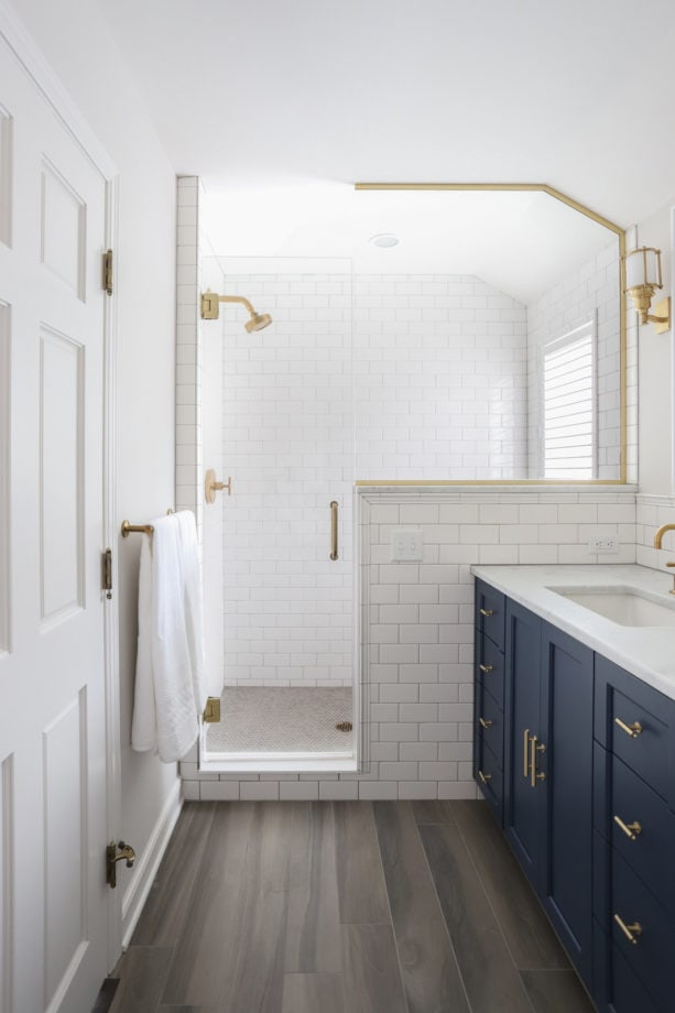 a small yet elegant bathroom with a navy blue cabinet and white tiles