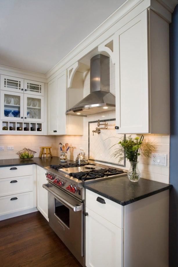 ceramic subway tile and soapstone liner backsplash behind stove with a pot filler