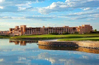 Hilton Santa Fe Buffalo Thunder resort across lake with blue New Mexico skies reflecting in the water
