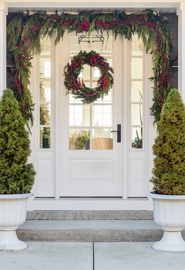 Christmas front porch decor. Gray house with evergreen trees and cedar garland.