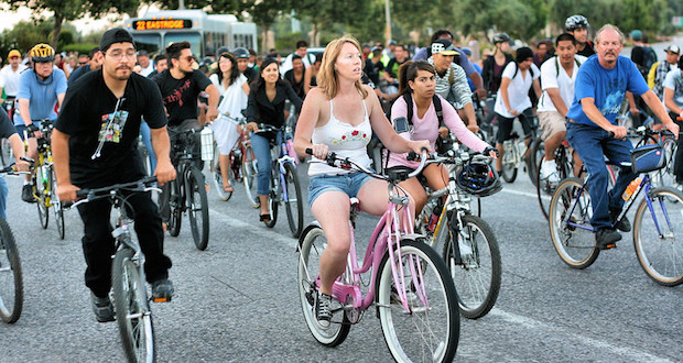 Woman on a pink cruiser bike in the middle of a bike rally