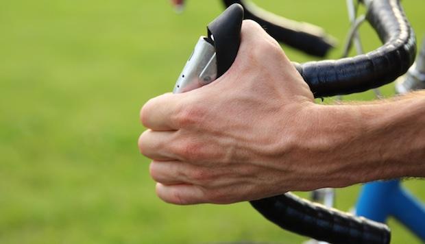 Hand squeezing the brake lever on a bike's handlebars
