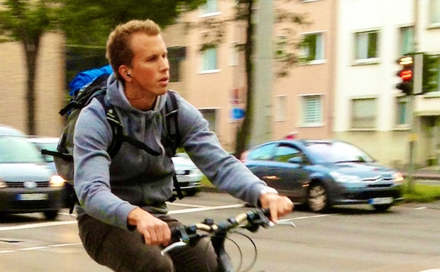 Cyclist cruising through an intersection with earbuds in his ears