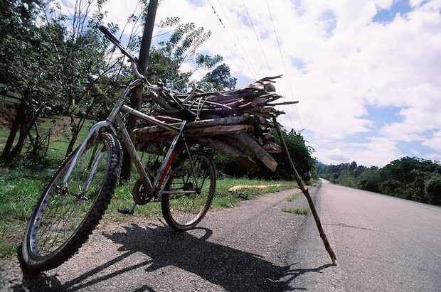 Bike carrying a load of wooden sticks is propped up by a wooden stick
