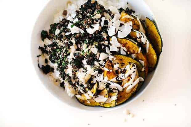 A white bowl on a white background. The bowl is filled with coconut kale, black lentils, roasted delicata squash and drizzled with dressing.