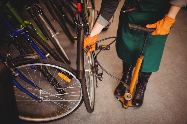Woman pumping a bike tire in a bike shop