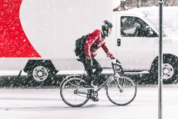 Cyclist commuting in the snow